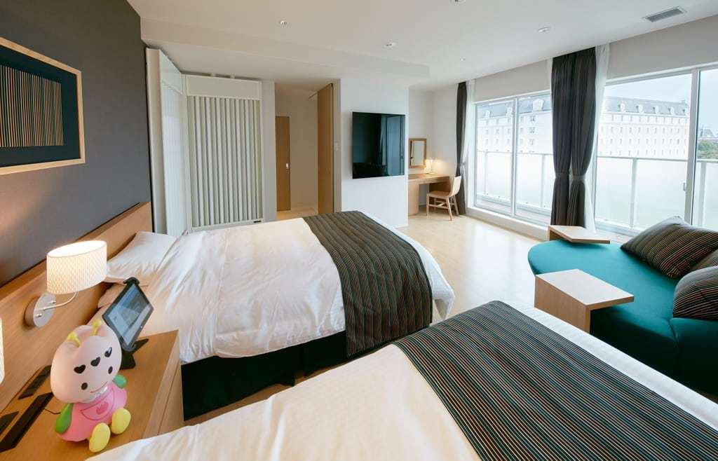 das Bild zeigt ein digitales Hotelzimmer, wo Roboter und Bots den Gast Service Leistungen erbringen